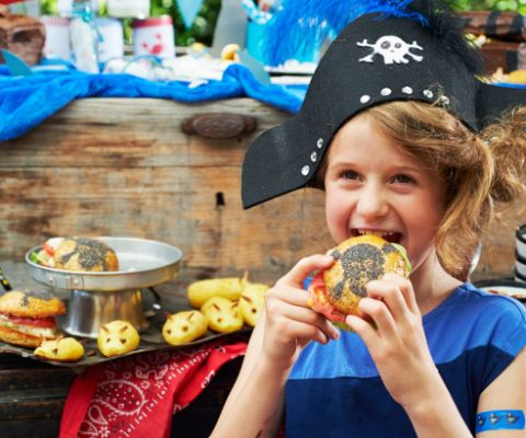 Enfant avec un chapeau de pirate devant un buffet de pirate
