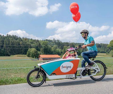 Vater fährt Famigros Cargo-Bike mit Kindern