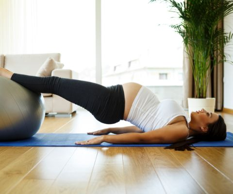 Donna incinta fa pilates in salotto