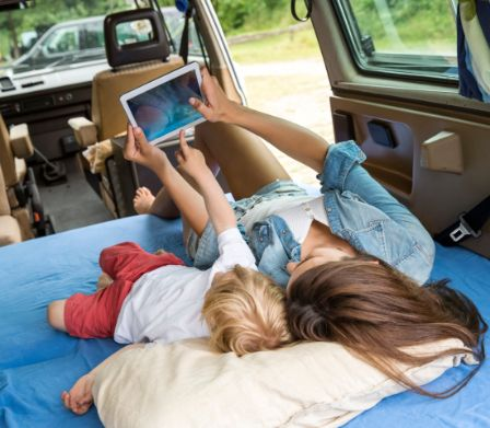 Mamma con bimbo distesi in auto con un tablet